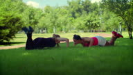 Woman push up exercise. Fitness woman pushing on green grass at park video