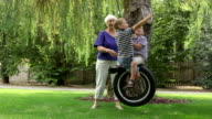 Woman pushing grandchildren on swing video