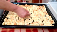 Woman puts baked golden puffs on the baking tray pan video