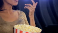 Woman puts her fingers on popcorn at the movie theater video