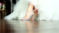 Woman puts on shoes hands close up shallow depth of field. Bride fastens zipper on luxurious high heeled sandals sitting in gorgeous white gown getting ready prepared for dancing at wedding ceremony video