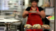 Woman puts pie on display at a bakery video