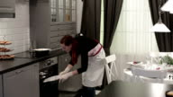 Woman puts plates of food in the oven video