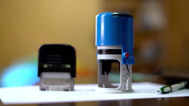 Woman puts print stamp on documents 4k. business video