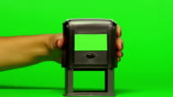 Woman puts print stamp on documents. Close up. Green screen video