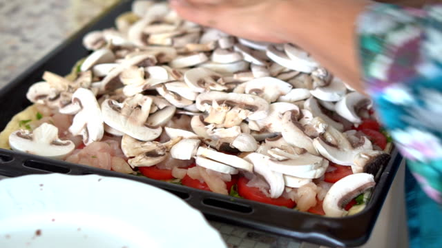A woman puts the ingredients on the dough for cooking pizza. Hands close up video