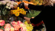 Woman puts vase of flowers on the shelves video