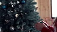 Woman putting balls at Christmas tree video