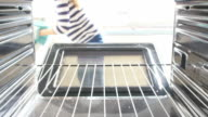 Woman Putting Dish Of Lasagne Into Oven To Cook video