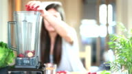 Woman putting fruits in blender for blending video