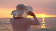 SLO MO Woman putting on her hat on the beach video