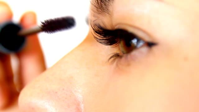 Woman putting on mascara, closeup video