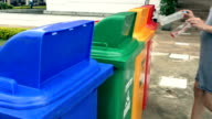Woman putting plastic bottles in recycle container. video