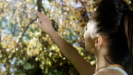 Woman raising hand to sun through autumnal trees. video