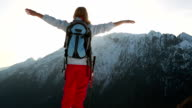 Woman reaches mountain top, outstretches arms video
