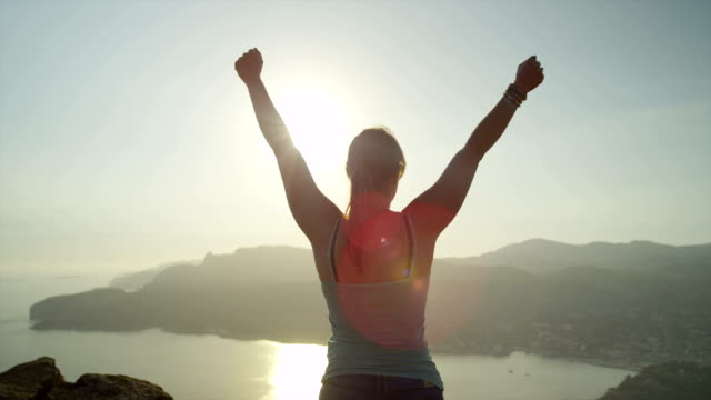 Woman reaches top of the mountain and raises her arms video