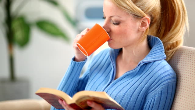 Woman reading a book and drinking tea video