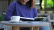 Woman reading a book at relax time with coffee video