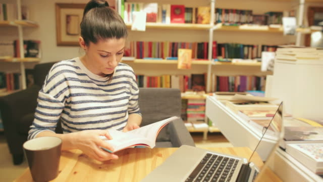 Woman reading a book in library. video