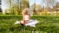 Woman reading a book in park, having a picnic video