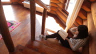 Woman reading a book on the cabin stairs. video