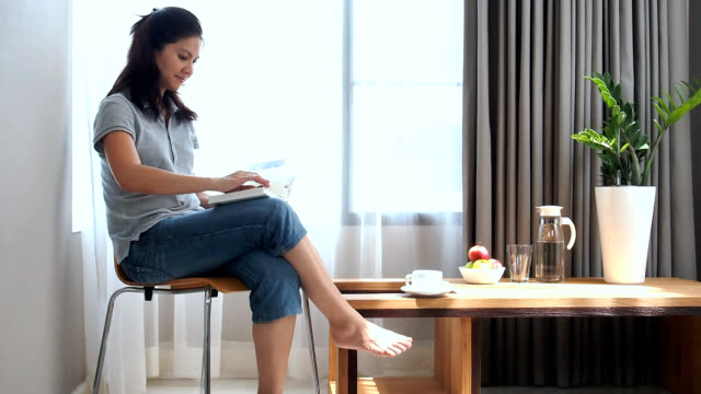 Woman reading book at home video