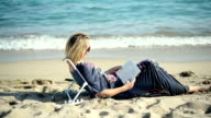 Woman reading book at the beach video