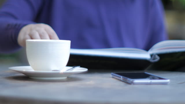 Woman reading book by the table in cafe with coffee video