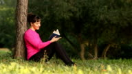 woman reading book in the nature video