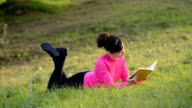 woman reading book lying in the meadow video