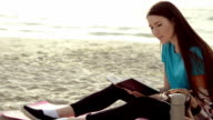 Woman reading book near the sea video