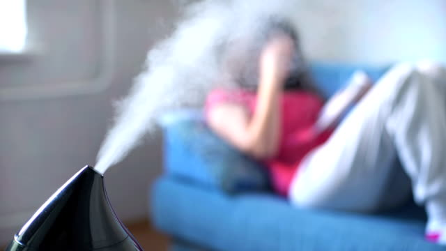Woman reading book on the background of working humidifier video