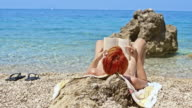 SLO MO Woman reading book on the beach video