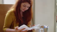 Woman Reading Menu in Sunlit Cafe video