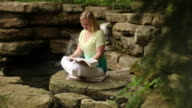 Woman reading near a waterfall video