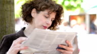 DOLLY: Woman reading newspaper outdoors video