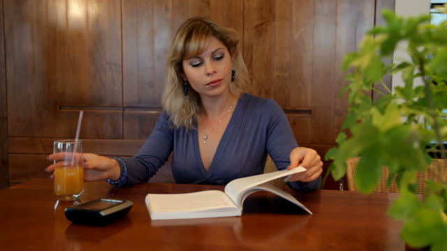 Woman reads book while waiting for someone video
