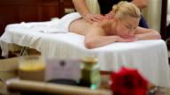 Woman receiving back massage at salon spa video
