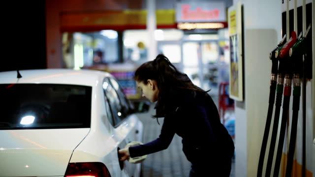 Woman refueling car at gas station pump at night video