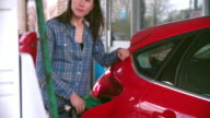 Woman refuelling a car at a petrol station video