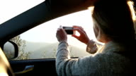 Woman relaxes in car, taking smart phone pic over hills video