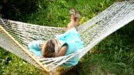 Woman relaxes in hammock in meadow, talks on phone video