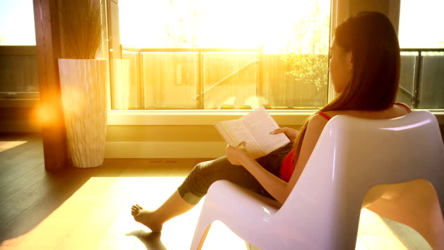 Woman relaxes in the evening sun reading a book video