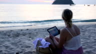 Woman relaxes on beach, uses digital tablet video
