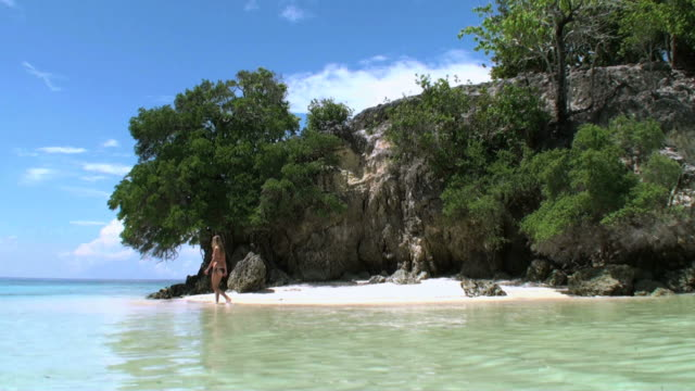 Woman relaxing and walking on lagoon of desert tropical island video