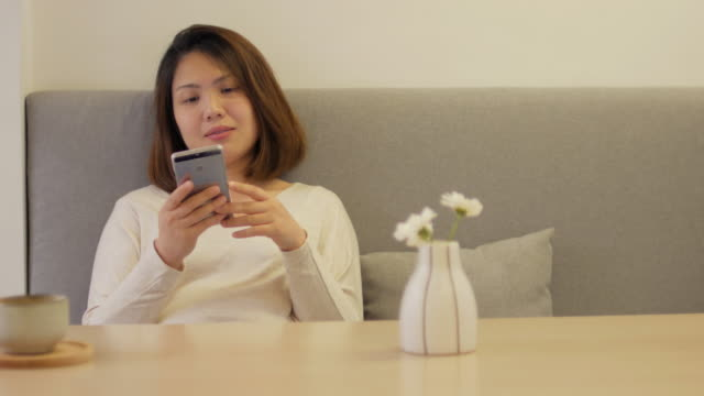 Woman relaxing at coffee cafe and using her smartphone on sofa , Dolly shot right to left video
