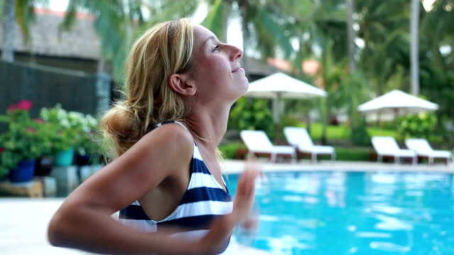 Woman relaxing by the pool, arms outstretched video
