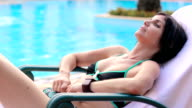 woman relaxing close  to the pool of the hotel resort during holidays video