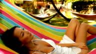 Woman relaxing in a hammock video
