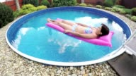 Woman relaxing in a small home pool video
